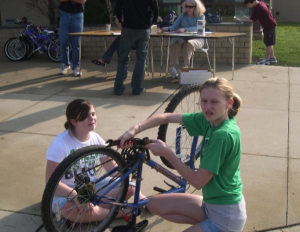 Students preparing a bicycle for the shipping container