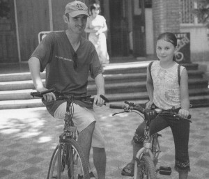 Slavic and Gabrielle with the bike she earned working in the shop