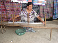 Isabel demonstrates how the threads are counted for the hand-loom.